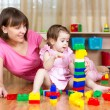 Stock Photo: Mother and her daughter play with toys at home interior