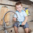 Funny kid boy washing dish on kitchen — Stock Photo #38637669