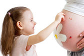 Child girl decorating pregnant mother's stomach — Foto de Stock