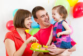Young family celebrating first birthday of baby girl — Stock Photo