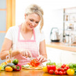 Cute woman cuts paprika for salad sitting at the kitchen table — Stock Photo