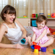 Mother, father and baby girl play musical toys. Isolated on whit — Stock Photo #38664455