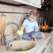 Little kid boy washing dish on kitchen — Stock Photo