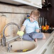 Little kid boy washing dish on kitchen — Stock Photo #38888453