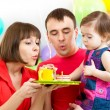 Stock Photo: Kid with parents celebrating birthday and blowing candles on ca