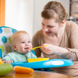Mom feeds funny baby with spoon — Stock Photo