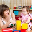 Stock Photo: Mom and kid play toys indoors
