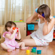 Stock Photo: Child and her mother playing together with toys