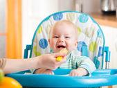 Mother spoon feeding baby boy — Stock Photo