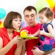 Kid with parents celebrating birthday and blowing candles on ca — Stock Photo #39367343