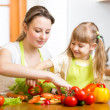 Mother teaching kid daughter preparing salad at kitchen — Stock Photo