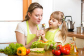 Mother feeding kid vegetables in kitchen — Stock Photo