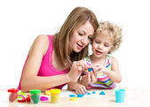 Child and mother play colorful clay toy — Stock Photo