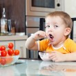 Child boy eating healthy food in kitchen  — Stock Photo #39992879