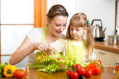 Happy woman and child preparing healthy food together — Stock Photo