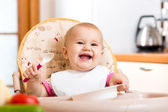 Smiling baby eating food on kitchen — Stock Photo