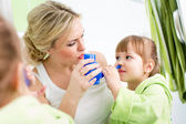 Mother and kid with neti pot ready for nasal irrigation or douch — Stock Photo