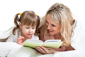 Mom reading to kid a book in the bed — Stockfoto