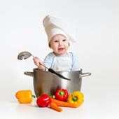 Cook baby sitting inside pan with healthy food — Stock Photo