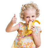 Kid girl eating banana and showing ok sign — Stockfoto