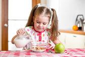 Kid girl preparing corn flakes with milk — Stock Photo