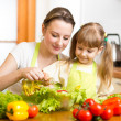 Happy womancooking with child at kitchen — Stock Photo #41250329