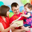 Smiling kid girl with mother and father opening gift box — Stock Photo #41527363