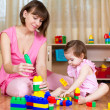 Mother and her kid play with block toys at home interior — Stock Photo #41527461