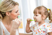 Mother and kid daughter brushing teeth in bathroom — Stock Photo