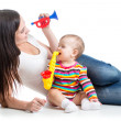 Stock Photo: Baby and mom play musical toys