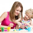 Stock Photo: Kid and mother play colorful clay toy