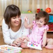 Stock Photo: Mother and kid play together in home interior