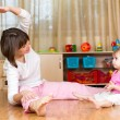 Stock Photo: Mom and kid doing exercises sitting on floor in home interio