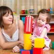 Mom and child play block toys indoors — Stock Photo