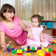 Stock Photo: Mom and child play with toys at home