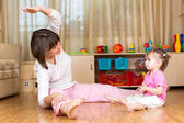 Mom and kid doing exercises sitting on the floor in home interio — Stock Photo