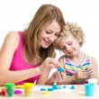 Stock Photo: Mom and daughter play colorful clay toy