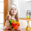 Стоковое фото: Kid girl weared as cook with vegetables at kitchen