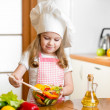 Stock Photo: Kid making salad at kitchen