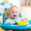 Stock Photo: Upset baby sitting in highchair for feeding