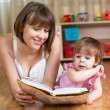 Stock Photo: Mother reading book to child at home