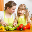 Young mother and her kid making vegetable salad — Stock Photo