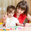 Stock Photo: Mom and kid girl paint together at home