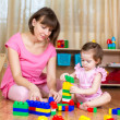 Stock Photo: Mom and kid girl playing block toys at home
