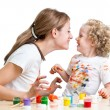 Stock Photo: Smiling mother and child girl painting together