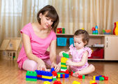 Mom and kid girl playing block toys at home — Stock Photo