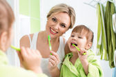 Mother and child daughter brushing teeth in bathroom — Stock Photo