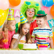 Kids blowing candle on festive cake — Stock Photo #42662543