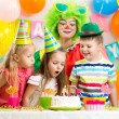 Kids blowing candle on festive cake — Stock Photo