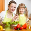 Young mother and her kid making vegetable salad — Stock Photo #42662547